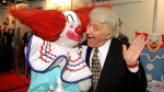 A man dressed as Bozo, left, poses with Bozo creator, Larry Harmon, in Las Vegas, on Jan. 24, 1996. (Lennox McLendon / AP)