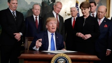 U.S. President Donald Trump signs a presidential memorandum imposing tariffs and investment restrictions on China in the Diplomatic Reception Room of the White House, Thursday, March 22, 2018, in Washington. (AP / Evan Vucci)
