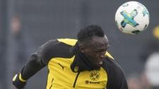 Usain Bolt heads the ball in Dortmund