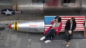 Chinese women sit on a bench with a U.S. flag theme outside an apparel store in Beijing, on March 23, 2018. (Ng Han Guan / AP)