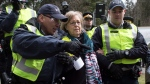 Federal Green Party Leader Elizabeth May, centre, is arrested by RCMP officers after joining protesters outside Kinder Morgan's facility in Burnaby, B.C., on Friday March 23, 2018. THE CANADIAN PRESS/Darryl Dyck