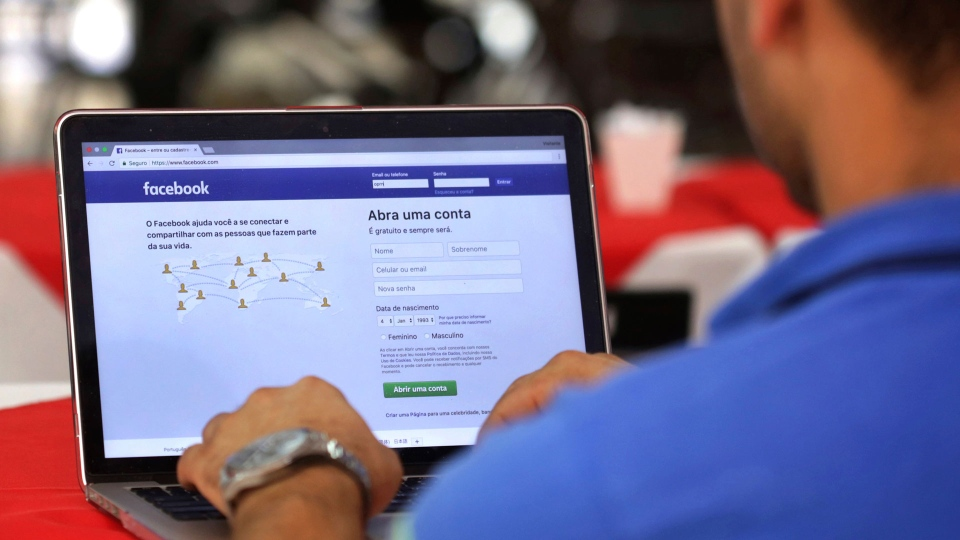 In this Thursday, Jan. 4, 2018, file photo, a man enters his Facebook page, at a restaurant in Brasilia, Brazil. (AP Photo/Eraldo Peres, File)