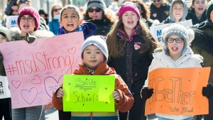 Eleven year old, Lexington Vickery, right, holds up signs during a 'March for Our Lives' rally to show solidarity with the U.S. gun control movement in Montreal, Saturday, March 24, 2018. THE CANADIAN PRESS/Graham Hughes
