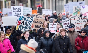 People hold up signs during a 'March for Our Lives' rally to show solidarity with the U.S. gun control movement in Montreal, Saturday, March 24, 2018. THE CANADIAN PRESS/Graham Hughes