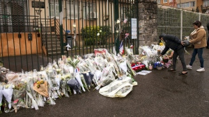 """A woman places flowers at the main gate of the Police headquarters in Carcassonne, France, Saturday, March 24, 2018, following an attack on a supermarket in Trebes in the south of the country on Friday. A French police officer who offered himself up to an Islamic extremist gunman in exchange for a hostage died of his injuries, raising the death toll in the attack to four, and the officer was honored Saturday as a national hero of """"exceptional courage and selflessness."""" (AP Photo/Emilio Morenatti)"""