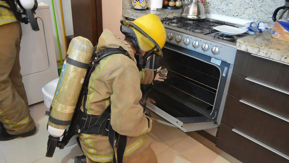 In this undated photo provided by the Quintana Roo Prosecutors Office, a firefighter examines a gas stove in the rented condo where an Iowa couple and their two children died in Tulum, Mexico. (Quintana Roo Prosecutor's Office via AP)
