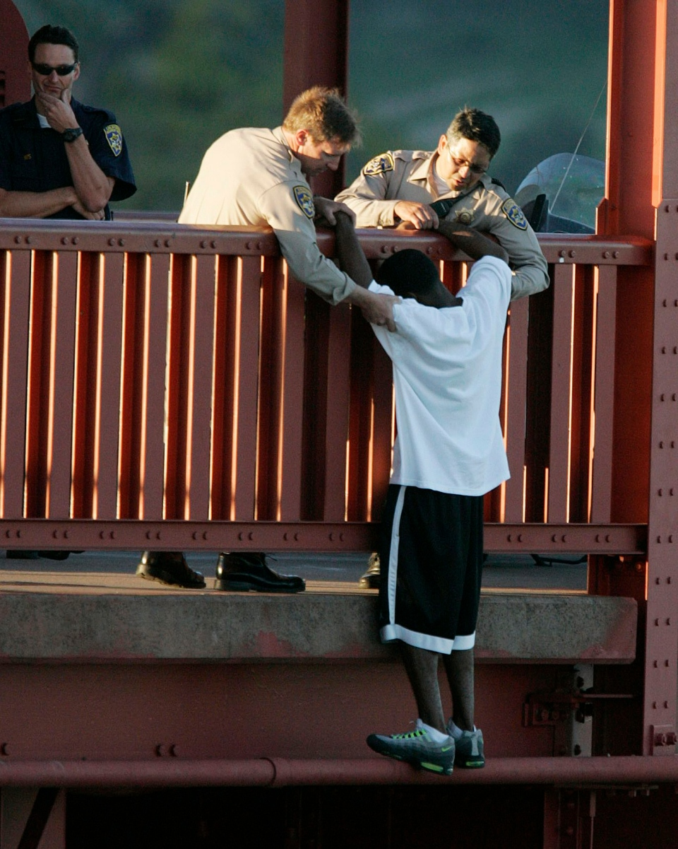 In this March 11, 2005 photo, Kevin Berthia is talked out of jumping off the Golden Gate Bridge and pulled to safety by California Highway Patrolman Kevin Briggs, center, in San Francisco. (AP Photo/The San Francisco Chronicle, John Storey)