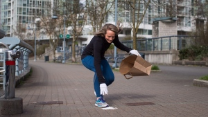 Melanie Knight picks up litter while jogging in Vancouver, B.C., on March 21, 2018. (Darryl Dyck / THE CANADIAN PRESS)