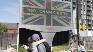 A couple embrace under a billboard in Manchester, England, on May 23, 2017. (Kirsty Wigglesworth / AP)