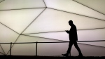 A man looks at his phone as he walks along the Samsung stand during the Mobile World Congress wireless show in Barcelona, Spain on February 27, 2017. THE CANADIAN PRESS/AP, Emilio Morenatti