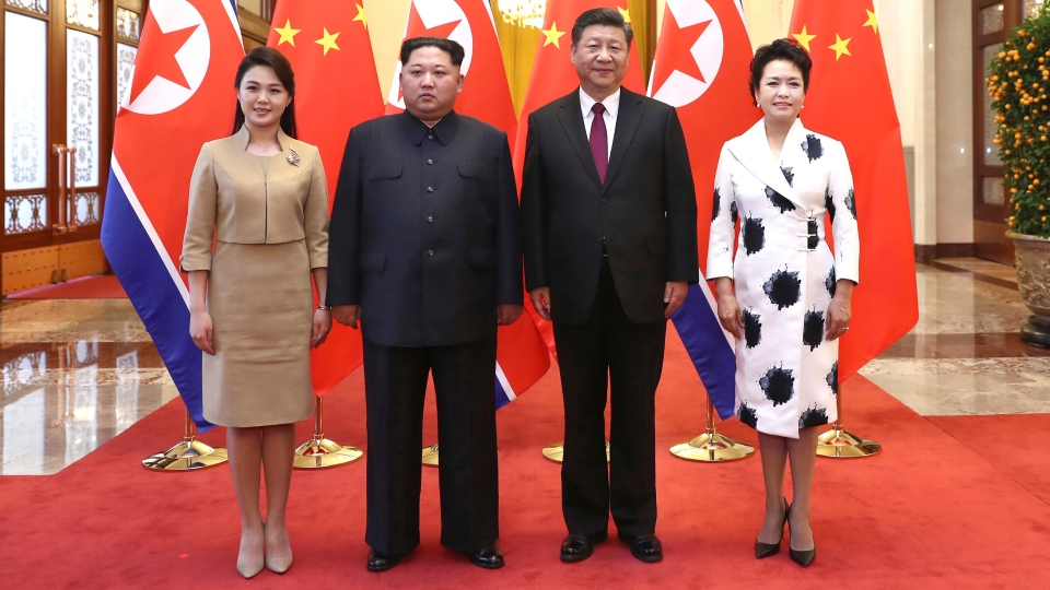 In this photo released Wednesday, March 28, 2018 by China's Xinhua News Agency, Chinese President Xi Jinping, second from right, and his wife Peng Liyuan, right, and North Korean leader Kim Jong Un, second from left, and his wife Ri Sol Ju, left, pose for a photo at the Great Hall of the People in Beijing. (Ju Peng/Xinhua via AP)