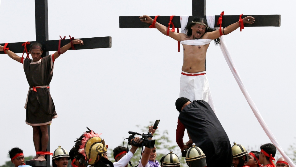 Ruben Enaje, right, grimaces as his feet are nailed to the cross for the 32nd time during a reenactment of Jesus Christ's sufferings as part of Good Friday rituals in the village of San Pedro Cutud, Pampanga province, northern Philippines Friday, March 30, 2018. (AP Photo/Aaron Favila)