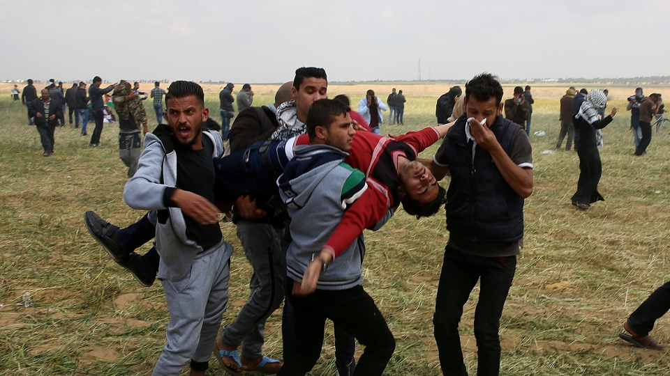Palestinian protesters evacuate a wounded youth during clashes with Israeli troops along the Gaza Strip border with Israel, east of Khan Younis, Gaza Strip, Friday, March 30, 2018. (AP / Adel Hana)