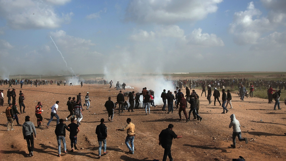 Palestinian protesters run for cover from teargas fired by Israeli troops during a demonstration near the Gaza Strip border with Israel, in eastern Gaza City, Friday, March 30, 2018. (AP / Khalil Hamra)