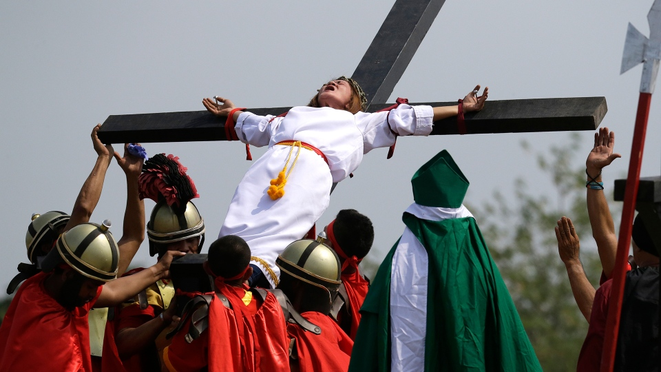 Maryjane Sazon, a 39-year-old beauty salon worker, grimaces after being nailed to the cross as part of Good Friday rituals in the village of San Pedro Cutud, Pampanga province, northern Philippines Friday, March 30, 2018. (AP / Aaron Favila)