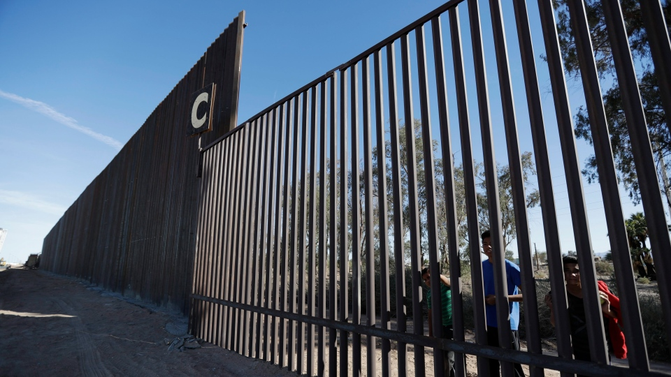 In this March 5, 2018, photo, boys look through an older section of the border structure from Mexicali, Mexico, alongside a newly-constructed, taller section, left, in Calexico, Calif. (AP Photo/Gregory Bull)