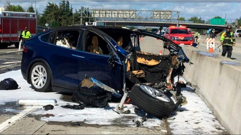 In this March 23, 2018 file photo provided by KTVU, emergency personnel work a the scene where a Tesla electric SUV crashed into a barrier on U.S. Highway 101 in Mountain View, Calif. (KTVU via AP)