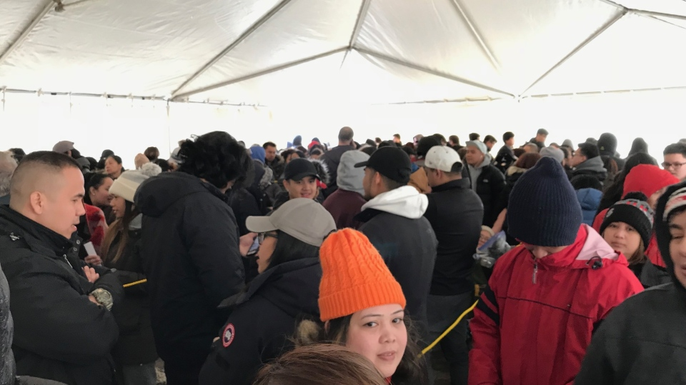 Customers wait in a tent to enter Jollibee's Toronto location, on Sunday, April 1, 2018.