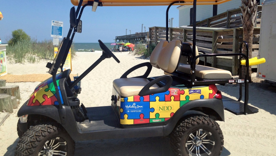This July 21, 2017 photo shows a Champion Autism Network golf cart decorated with puzzle pieces, a symbol for autism, in Surfside, S.C., with the Surfside Pier in the background. The golf cart is sponsored by area businesses who purchase puzzle pieces and get their logos printed on them. (Becky Large via AP)