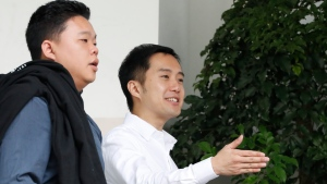 In this Jan. 16, 2018, photo, Terence Tan En Wei, 35, right, and Yao Songlaing, 34, leave the State Court in Singapore. (AP Photo/Yong Teck Lim)