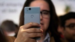 A woman looks at a Google Pixel 2 phone at a Google event at the SFJAZZ Center in San Francisco, October 4, 2017. (THE CANADIAN PRESS/AP, Jeff Chiu)