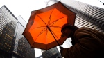 A pedestrian shields himself from rain under an umbrella in downtown Toronto Friday, March 4, 2011. THE CANADIAN PRESS/Darren Calabrese