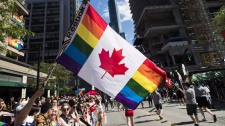A man holds a flag on a hockey stick during the Pride parade in Toronto on June 25, 2017.THE CANADIAN PRESS/Mark Blinch