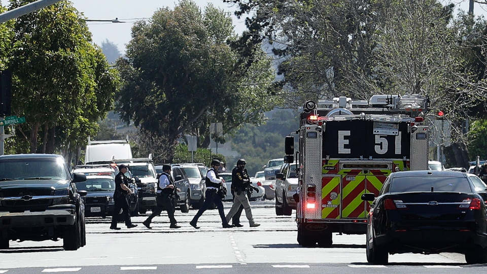 Officers walk near a YouTube office in San Bruno, Calif., Tuesday, April 3, 2018. Police in Northern California are responding to reports of a shooting at YouTube headquarters in the city of San Bruno. (AP Photo/Jeff Chiu)