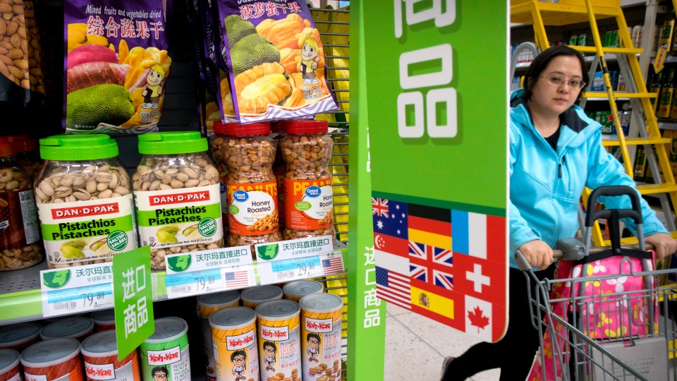 In this March 23, 2018. file photo, a woman pushes a shopping cart past a display of nuts imported from the United States at a supermarket in Beijing. (AP Photo/Mark Schiefelbein, File)