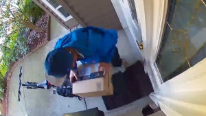A man is seen taking an Amazon package from the doorstep of a Richmond B.C. home on Monday, April 2, 2018. (Reddit)
