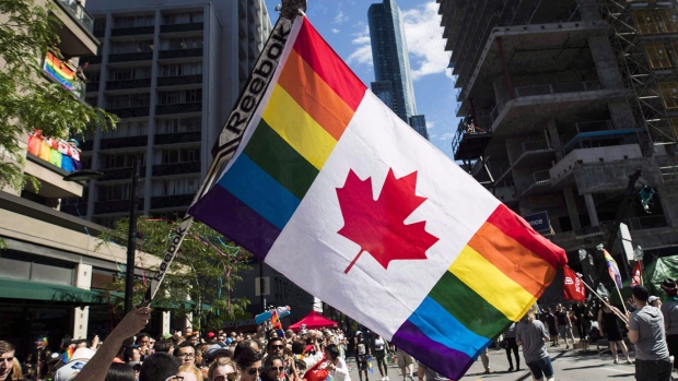 A man holds a flag on a hockey stick during the Pride parade in Toronto on June 25, 2017.  THE CANADIAN PRESS/Mark Blinch