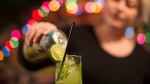 Bar owner Rachel Conduit makes a drink in a glass containing a recycled straw in Toronto's Farside bar on Tuesday, December 5, 2017. THE CANADIAN PRESS/Chris Young