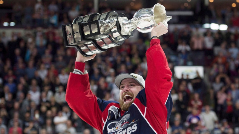 Windsor Spitfires center Aaron Luchuk, who scored the game winning goal, raises the trophy after defeating the Erie Otters to win the Memorial Cup in Windsor, Ont., on Sunday, May 28, 2017. (Adrian Wyld/THE CANADIAN PRESS)