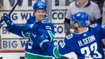 Vancouver Canucks' Daniel Sedin, left, celebrates his goal with his twin brother Henrik Sedin during second period NHL hockey action against the Arizona Coyotes, in Vancouver on Thursday, April 5, 2018. THE CANADIAN PRESS/Darryl Dyck