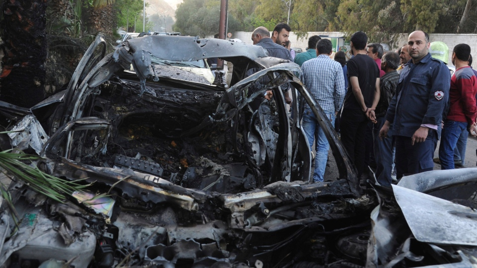 This photo released by the Syrian official news agency SANA, shows Syrians gathered next to a burnt car hit by a shelling by members of the Army of Islam rebel group at Rabwa neighborhood in Damascus, Syria, Friday, April 6, 2018. (SANA via AP)