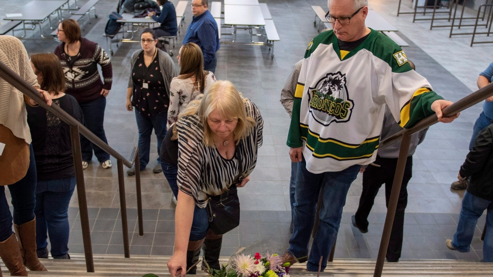 Humboldt mayor Rob Muench, in the Broncos jersey, along with other mourners lay down flower on the stairs that enter to Elgar Petersen Arena, home of the Humboldt Broncos, in Humboldt, Sask., on Saturday, April 7, 2018. THE CANADIAN PRESS/Liam Richards
