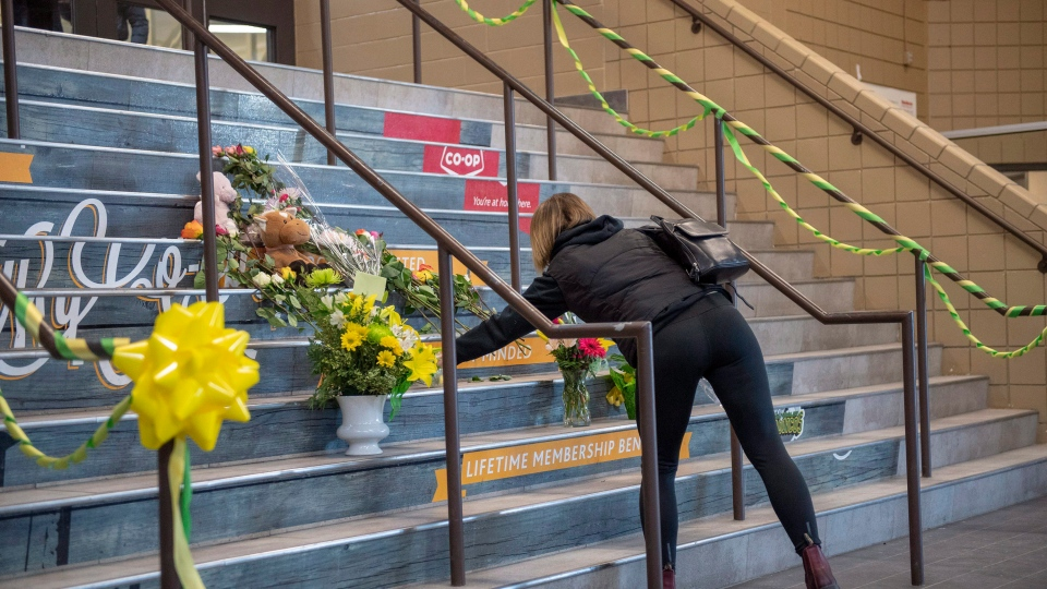 A woman lays flowers at a memorial on the stairs leading into Elgar Petersen Arena, home of the Humboldt Broncos hockey team, in Humboldt, Sask., on Saturday, April 7, 2018.  THE CANADIAN PRESS/Liam Richards
