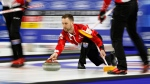 Canada skip Brad Gushue, center, delivers a stone against Sweden during the World Men's Curling Championship, April 6, 2018, in Las Vegas. (AP Photo/John Locher)
