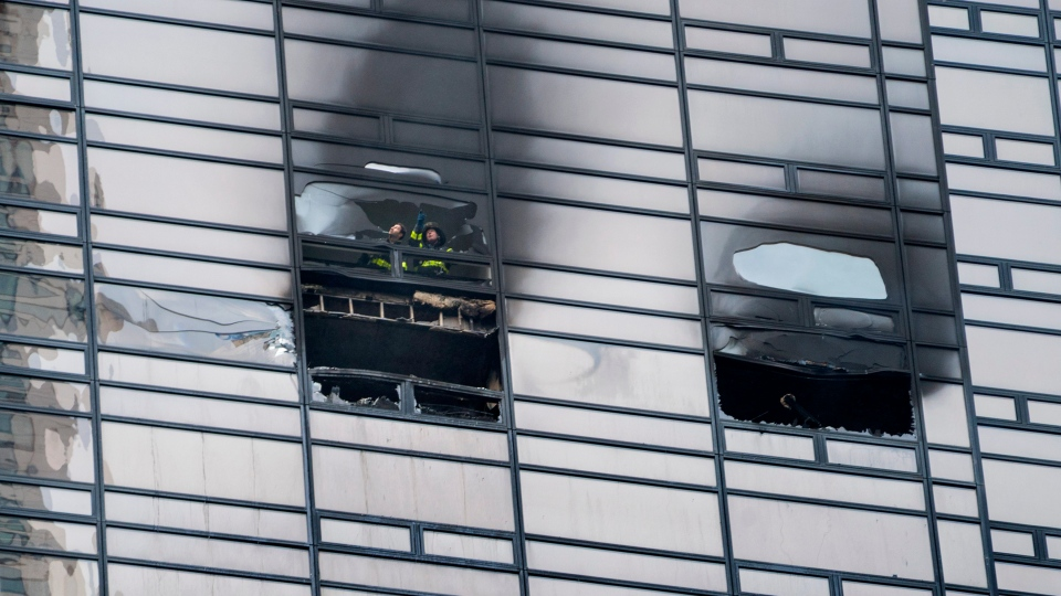 Firefighters look out from the window of a fire damaged apartment in Trump Tower in New York on Saturday, April 7, 2018. (AP Photo/Craig Ruttle)