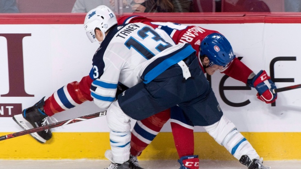 Winnipeg Jets' Brandon Tanev and Montreal Canadiens' Michael McCarron battle for the puck during first period NHL hockey action Tuesday, April 3, 2018 in Montreal. THE CANADIAN PRESS/Paul Chiasson