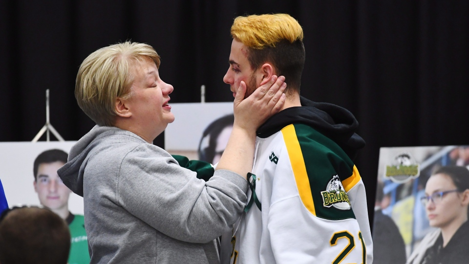 Humboldt Broncos' Nick Shumlanski, who was released from hospital earlier today, is comforted by a mourner during a vigil at the Elgar Petersen Arena, home of the Humboldt Broncos, to honour the victims of a fatal bus accident in Humboldt, Sask. on Sunday, April 8, 2018. (THE CANADIAN PRESS/Jonathan Hayward)