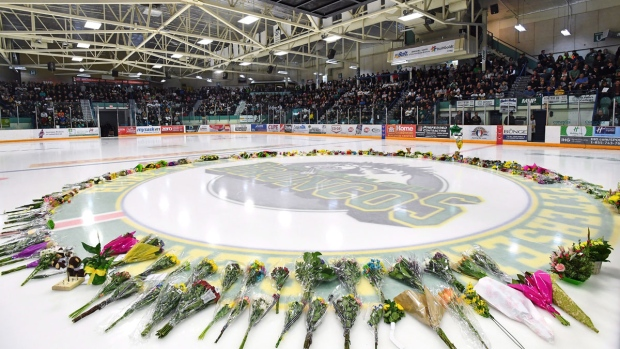 Flowers lie at centre ice as people gather for a v