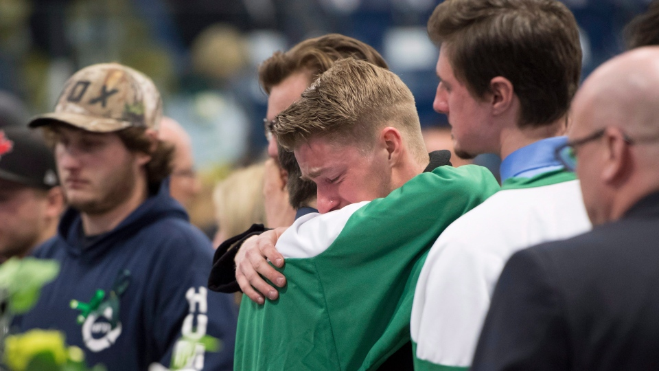 Mourners comfort each other during a vigil at the Elgar Petersen Arena, home of the Humboldt Broncos, to honour the victims of a fatal bus accident in Humboldt, Sask. on Sunday, April 8, 2018. (THE CANADIAN PRESS/Jonathan Hayward)