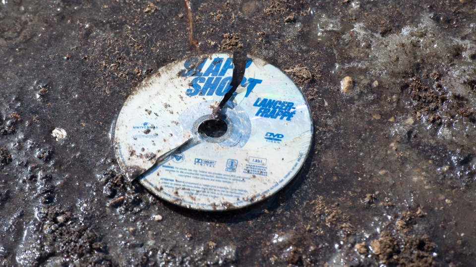 A broken DVD of the hockey movie Slap Shot is seen in the mud at the intersection of a crash site near Tisdale, Sask., Sunday, April 8, 2018. THE CANADIAN PRESS/Jonathan Hayward