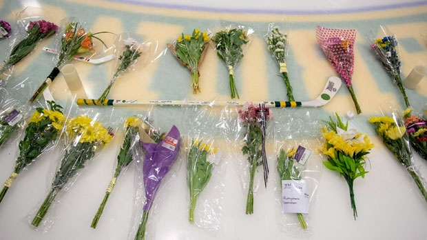 Flowers and other items continue to be added to a memorial on centre ice at Elgar Petersen Arena in Humboldt, Sask., on Monday, April 9, 2018. 15 people traveling with the Humboldt Broncos SJHL hockey team are dead, and many injured when their bus was collided with a semi-trailer 30 kilometres north of Tisdale, Sask.THE CANADIAN PRESS/Liam Richards