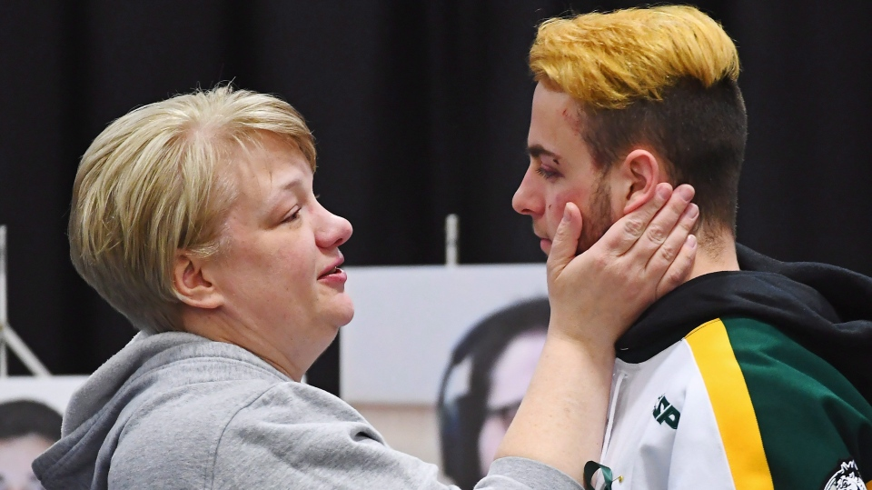 Humboldt Broncos bus crash survivor Nick Shumlanski, who was released from hospital, is comforted by a mourner during a vigil at the Elgar Petersen Arena, in Humboldt, Sask. on Sunday, April 8, 2018. (THE CANADIAN PRESS/Jonathan Hayward)