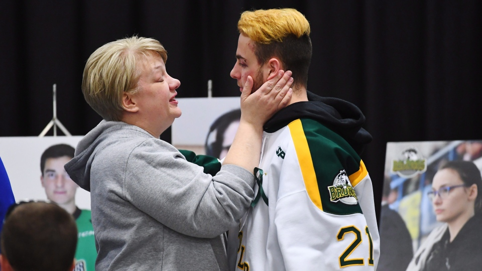 Humboldt Broncos' Nick Shumlanski is comforted by a mourner during a vigil at the Elgar Petersen Arena to honour the victims of a fatal bus accident in Humboldt, Sask. on Sunday, April 8, 2018. (Jonathan Hayward/THE CANADIAN PRESS)