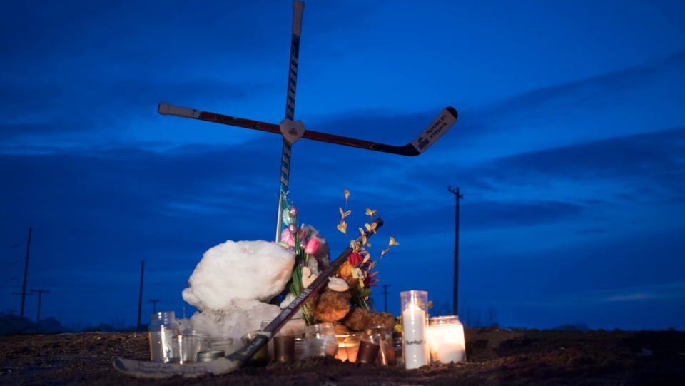 A cross made of hockey sticks is seen at a makeshift memorial at the intersection of a fatal bus crash near Tisdale, Sask., Monday, April, 9, 2018. (THE CANADIAN PRESS/Jonathan Hayward)