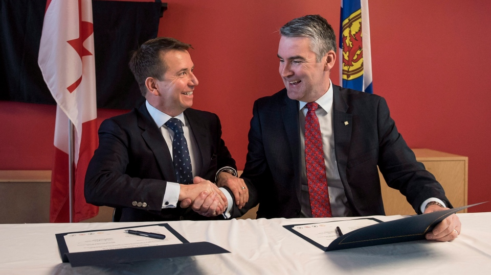 Scott Brison, left, MP for Kings-Hants, and Nova Scotia Premier Stephen McNeil shake hands after signing a bilateral agreement for more than $828 million over the next decade for infrastructure projects in Nova Scotia during a press conference in Halifax on Tuesday, April 10, 2018. (THE CANADIAN PRESS/Darren Calabrese)