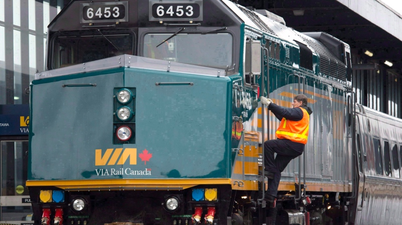 A Via Rail employee climbs aboard a locomotive at the train station in Ottawa on December 3, 2012. THE CANADIAN PRESS/Adrian Wyld
